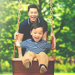 Dad in Park with Son on Swing